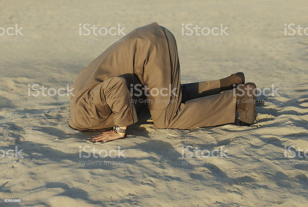 Businessman with head stuck in sand at the beach stock photo