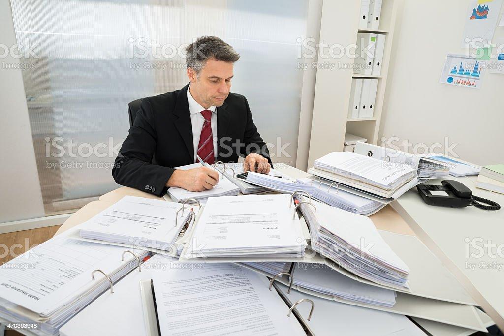 Businessman With Heap Of Folders On Desk stock photo