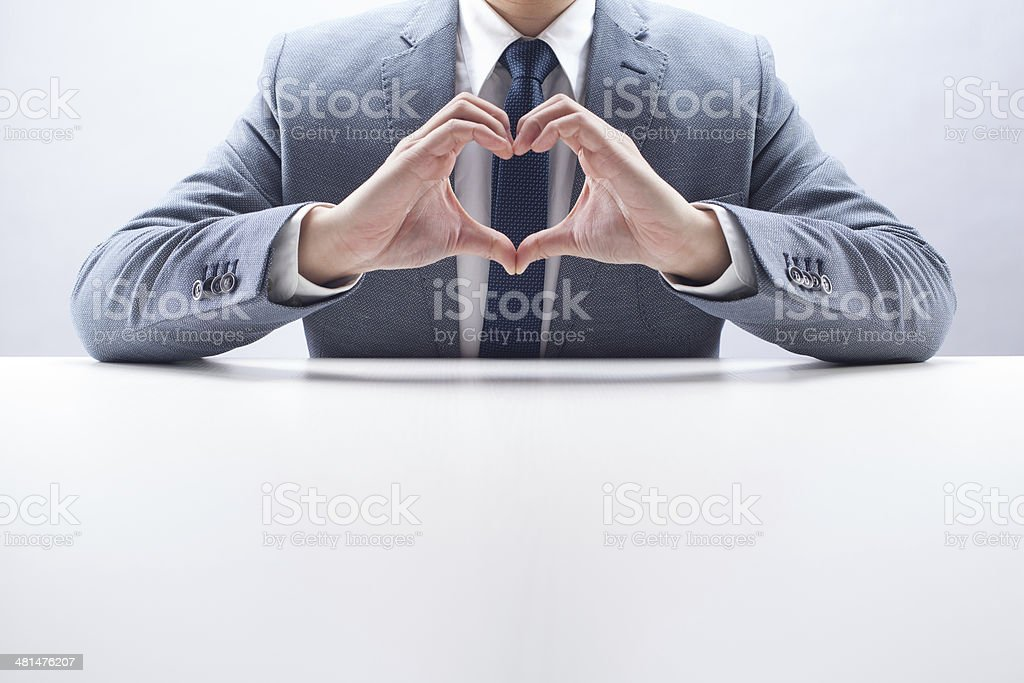 Businessman with Heart Hand Gesture stock photo