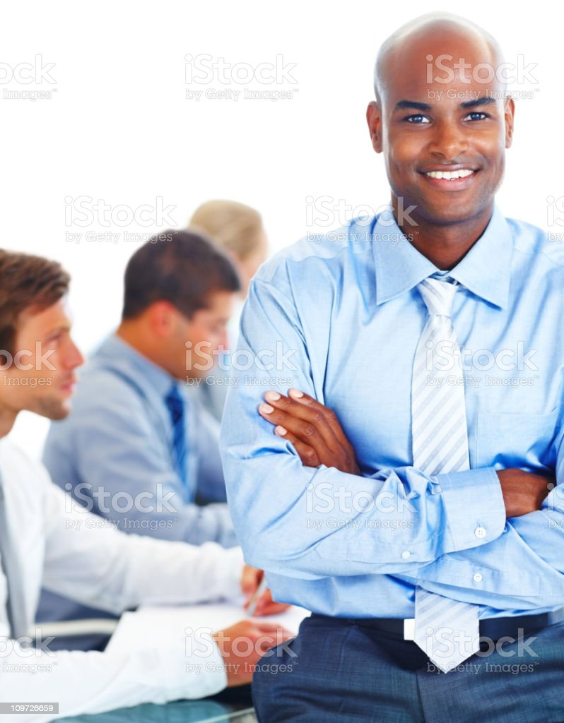 A businessman with his arms crossed, smiling with colleagues royalty-free stock photo