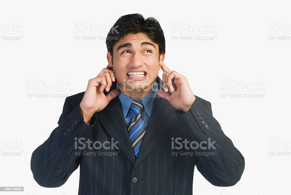Businessman with his fingers in ears stock photo