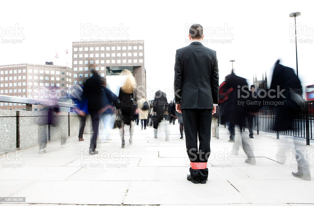 Businessman with his legs tied together in a crowd stock photo
