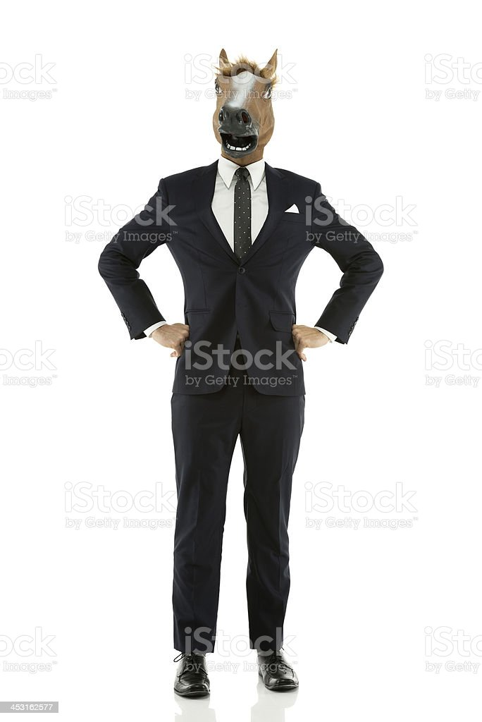 Businessman with horse's head posing against white royalty-free stock photo