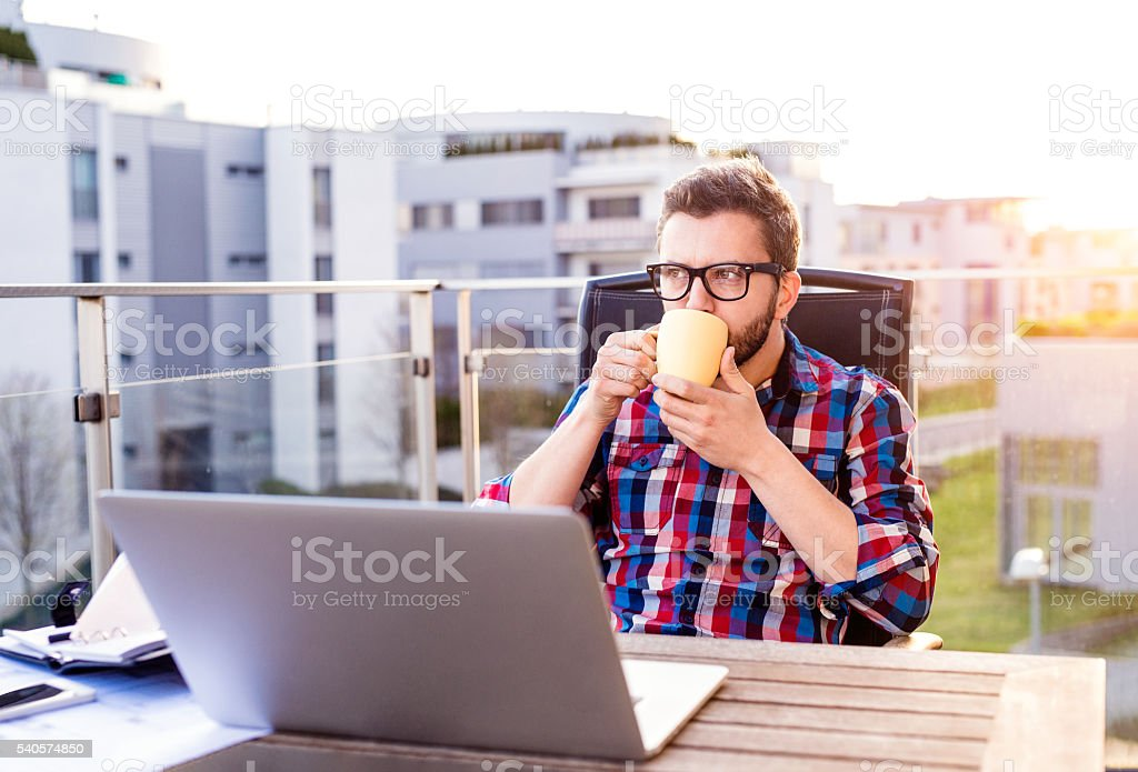 Businessman with laptop and cup of coffee, resting stock photo