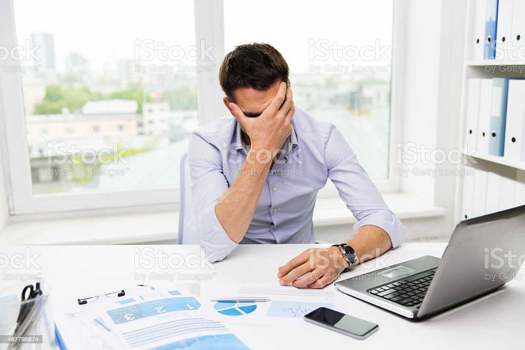 businessman with laptop and papers in office stock photo