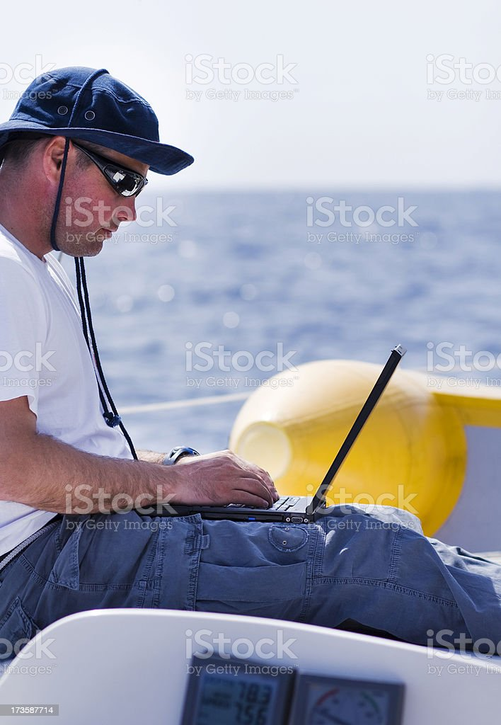Businessman with laptop on sailboat royalty-free stock photo