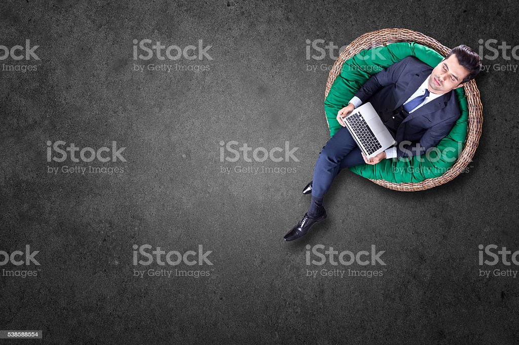 Businessman with laptop resting on chair stock photo