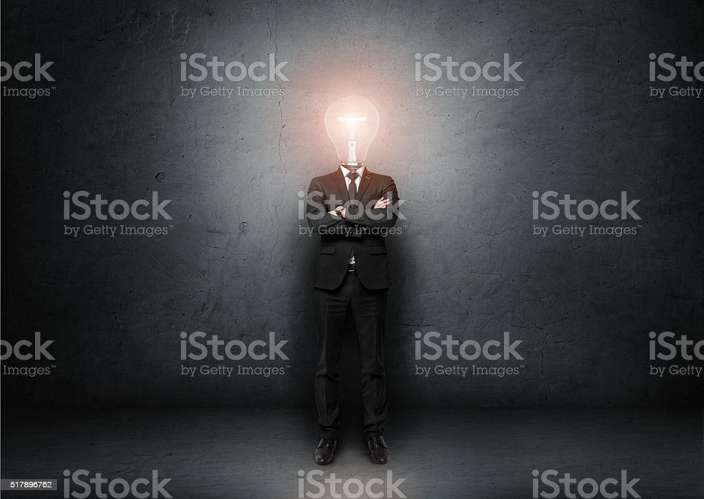 Businessman with light bulb instead of head on concrete room stock photo