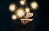 businessman with lightbulb on tablet concept inspiration or idea