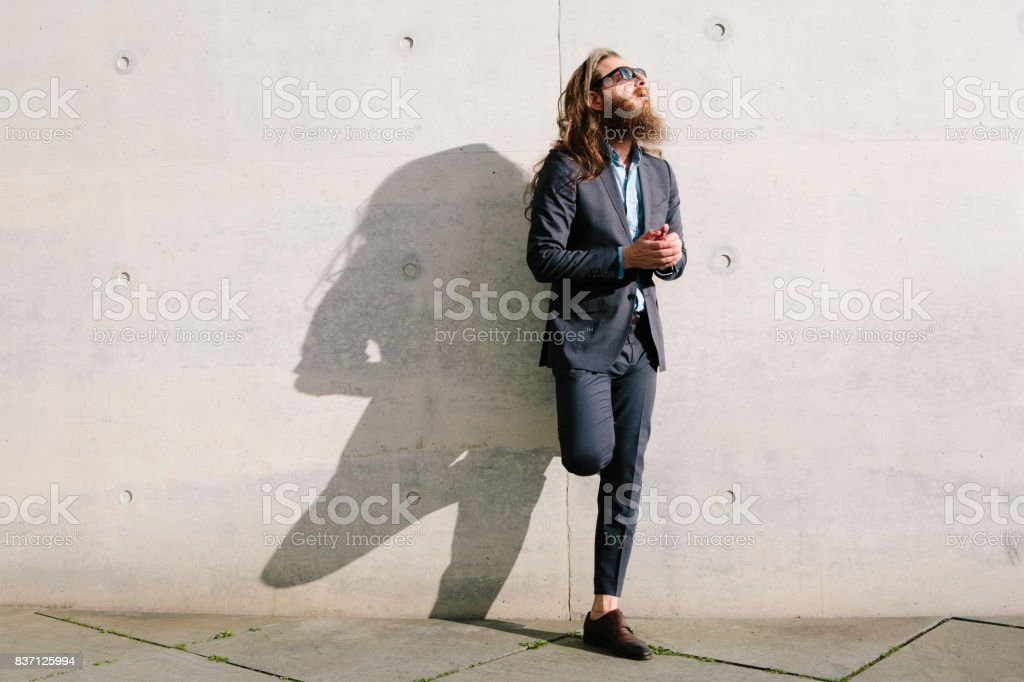 businessman with long hair and beard in front of concrete wall stock photo