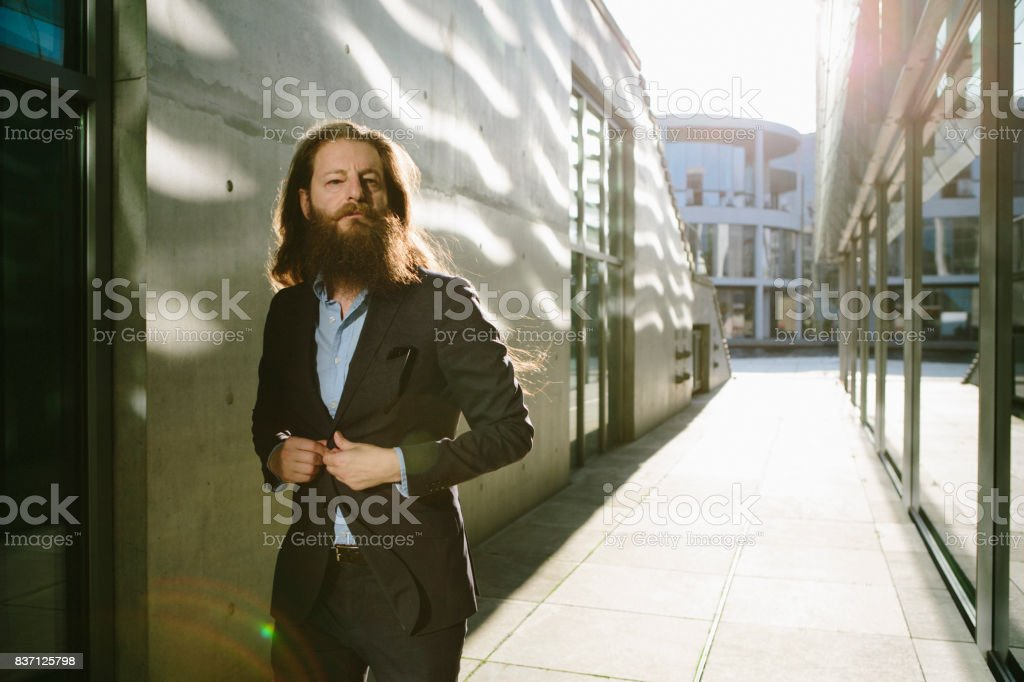 businessman with long hair and beard walks his way stock photo