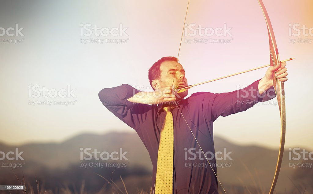 Businessman with longbow hiting the point stock photo