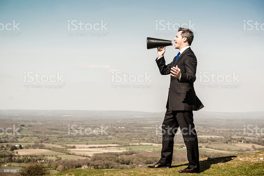 Businessman with loudhailer megaphone on hill stock photo