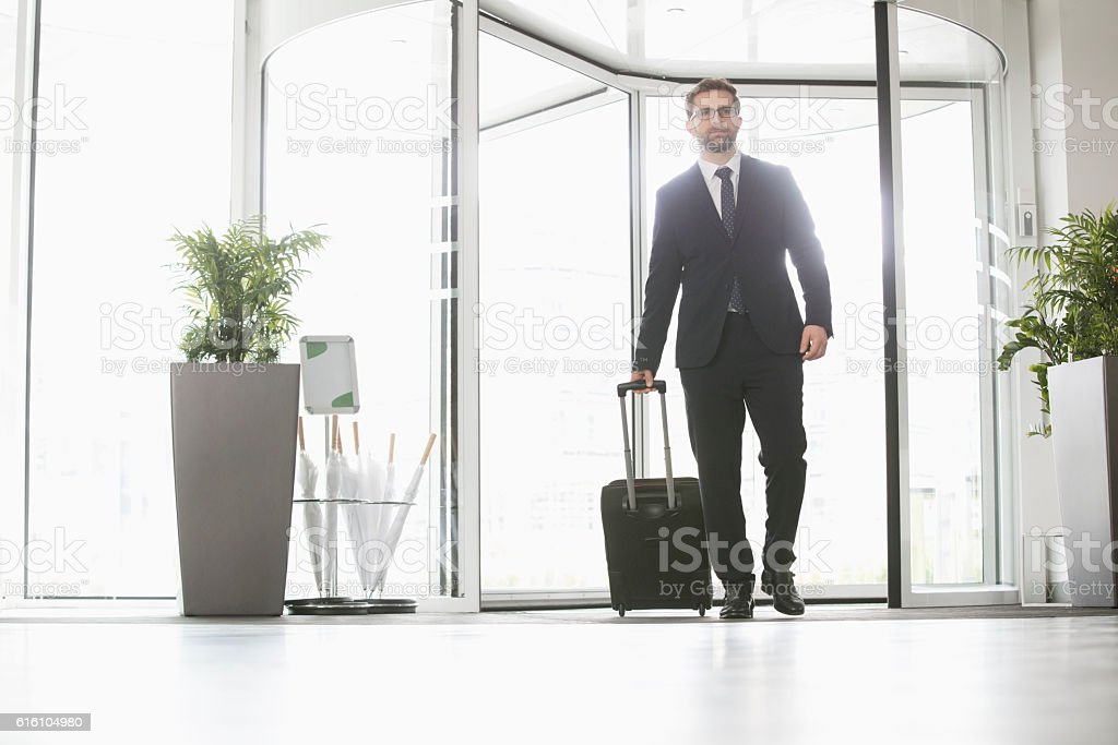 Businessman with luggage entering convention center stock photo