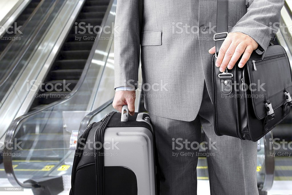 Businessman with luggage standing beside an escalator royalty-free stock photo