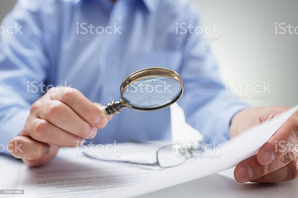 Businessman with magnifying glass reading documents stock photo