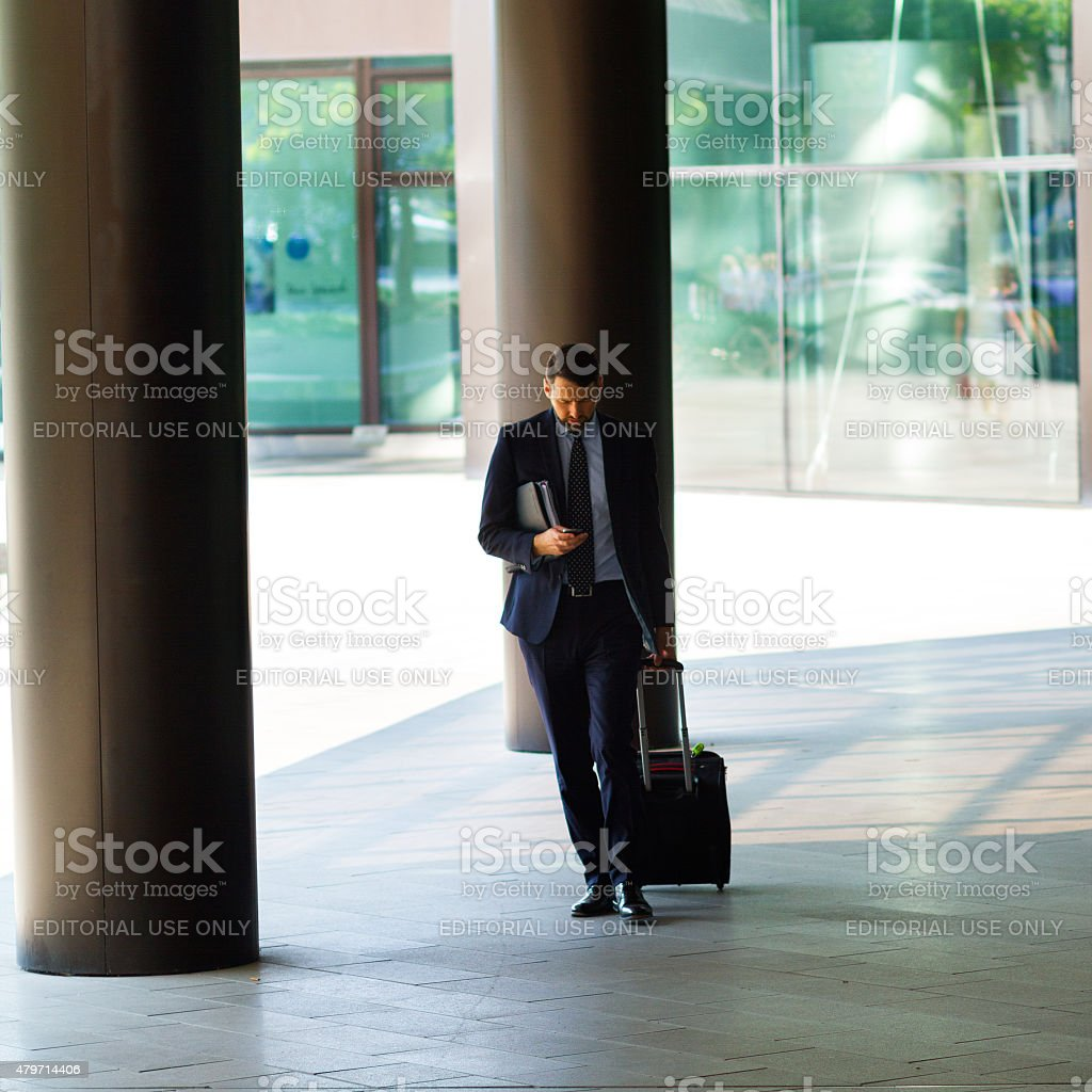 Businessman with mobile and luggage stock photo