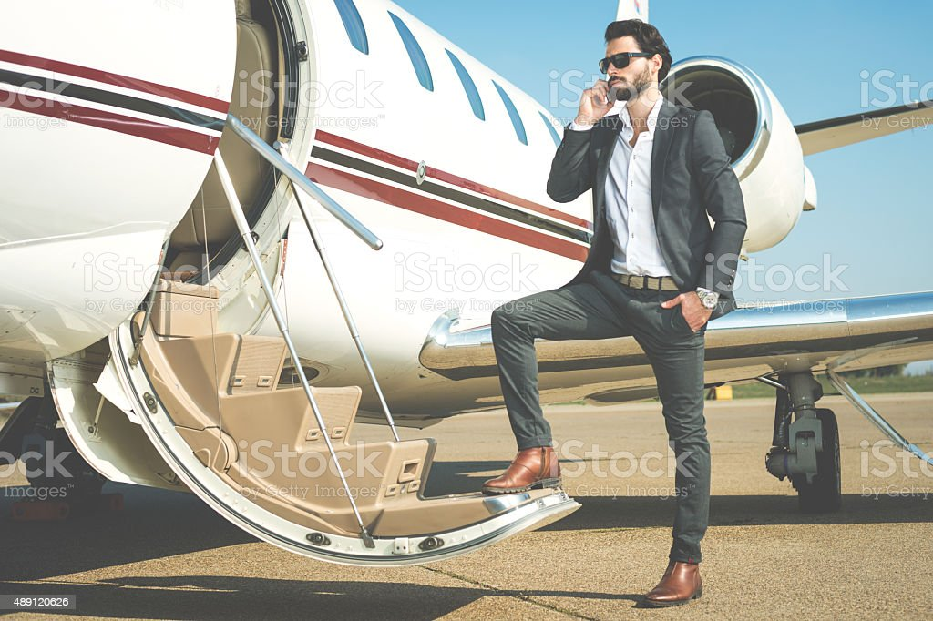 Businessman with mobile phone entering the private jet stock photo