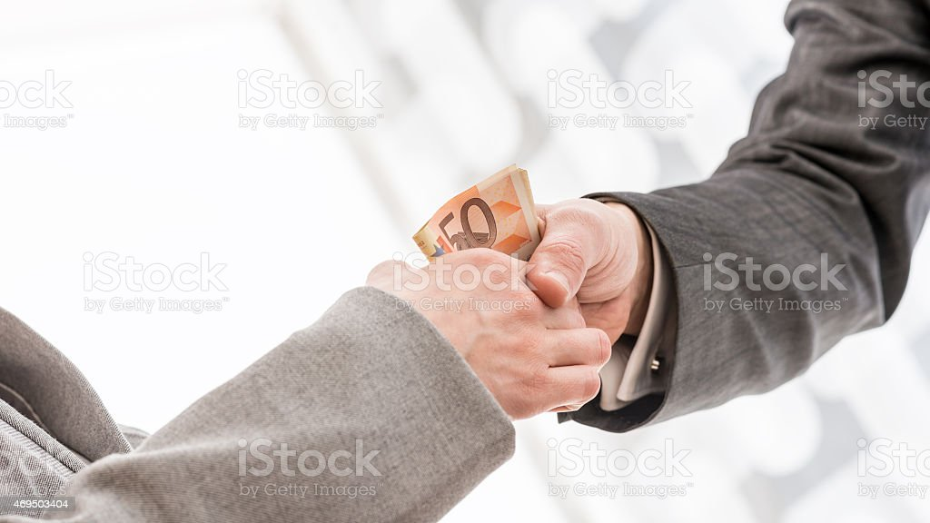 Businessman with Money Handshaking with Partner stock photo
