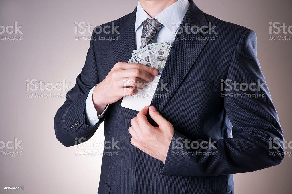 Businessman with money in studio. Corruption concept. Hundred dollar bills stock photo