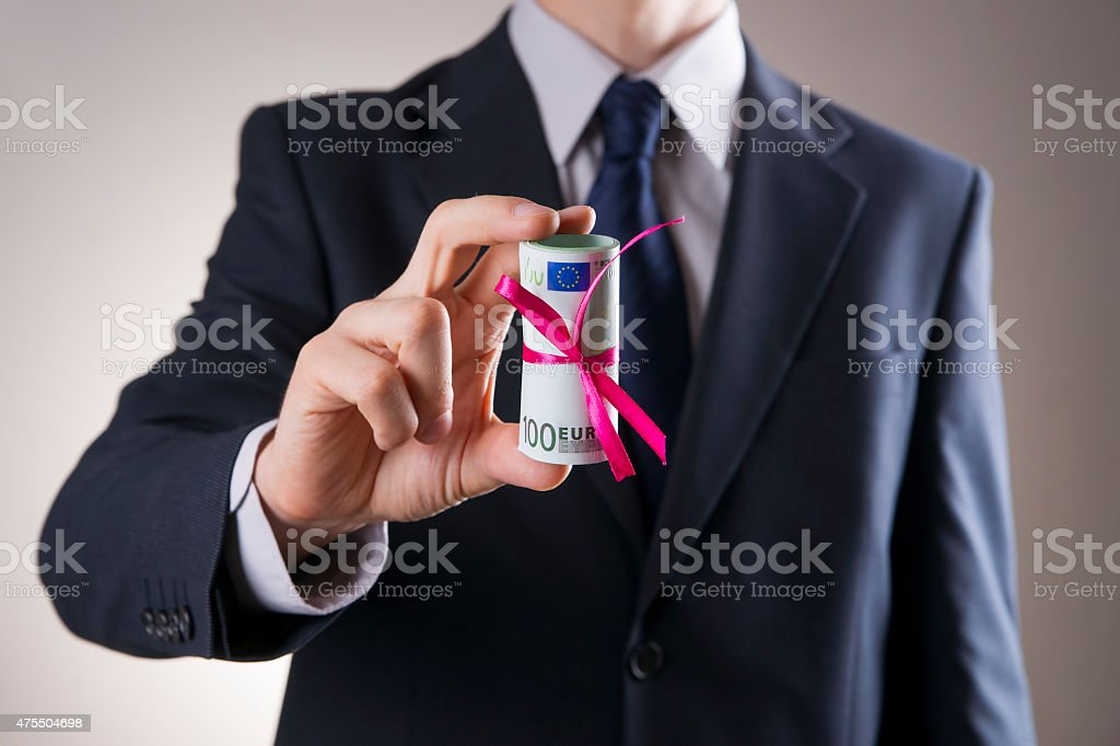 Businessman with money with bow in male hand stock photo