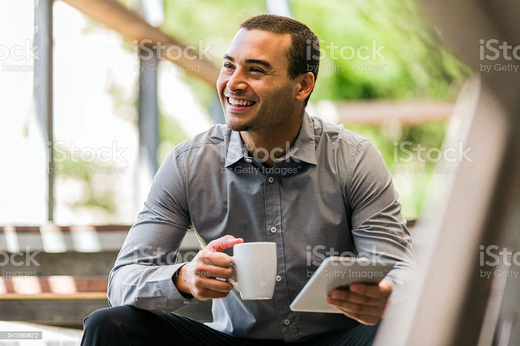 Businessman with mug and digital tablet on steps stock photo