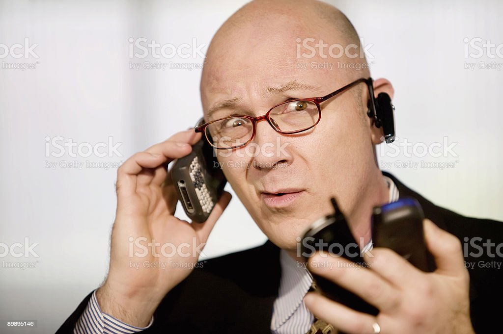 Businessman with multiple cell phones royalty-free stock photo