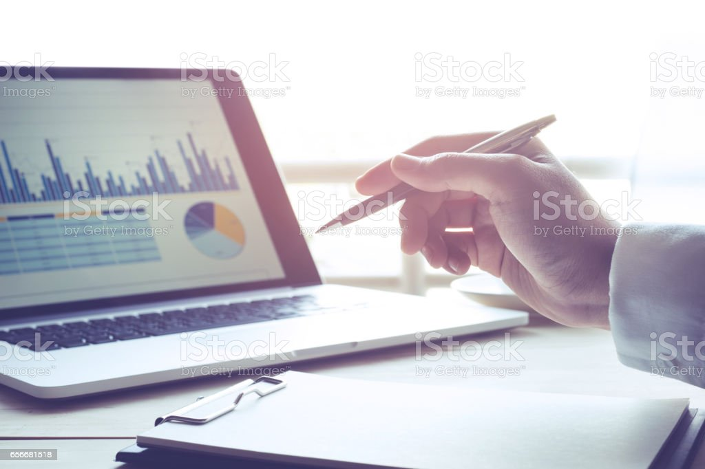 Businessman with notebook and modern laptop with graph stock photo