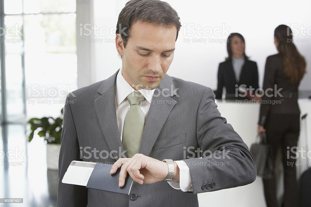 Businessman with passport checking time stock photo