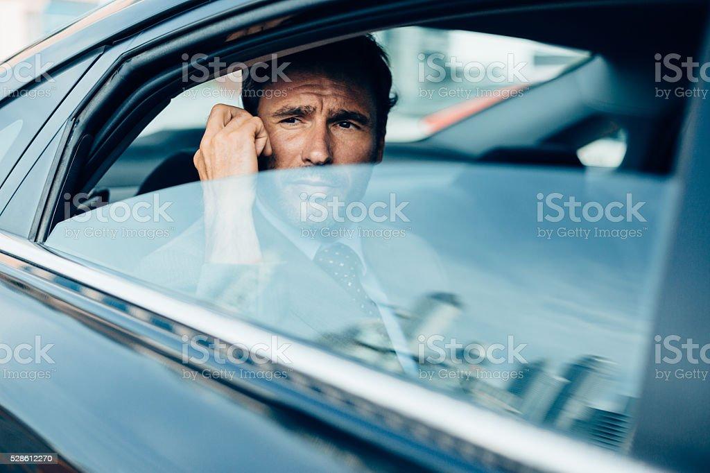 Businessman with phone inside dark car stock photo
