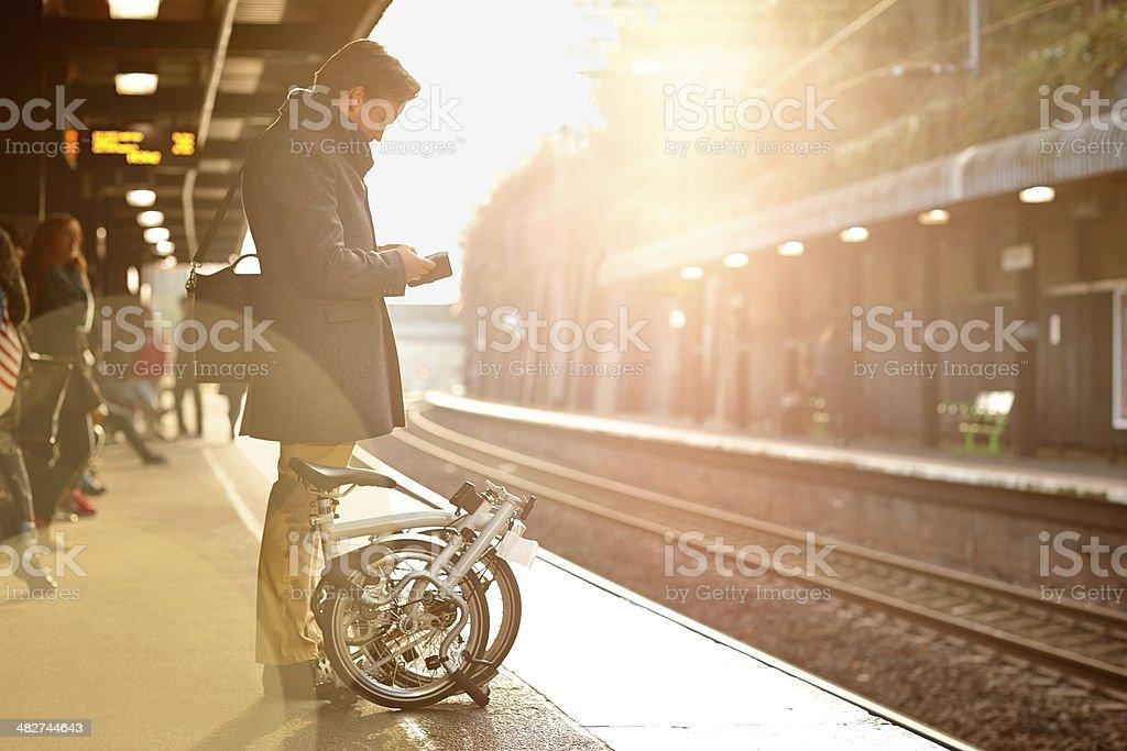 Businessman with phone on train platform stock photo