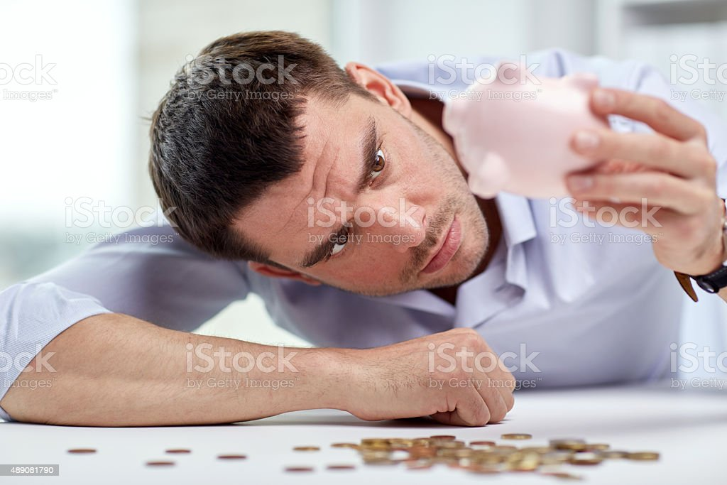 businessman with piggy bank and coins at office stock photo