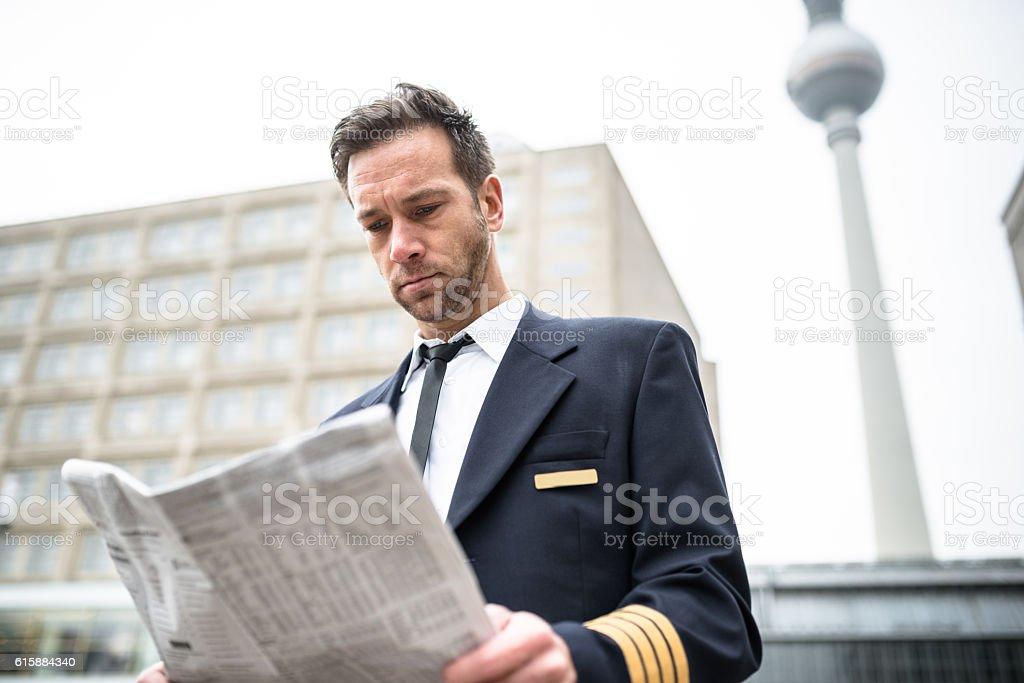 Businessman with pilot uniform reading the newspaper stock photo