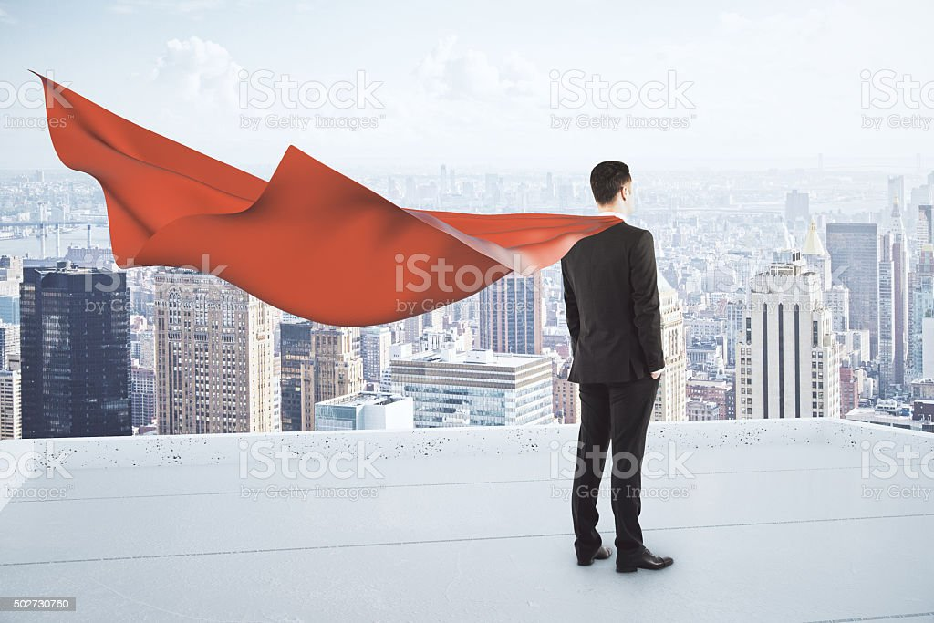 Businessman with red cape staying on the roof of skyscraper stock photo