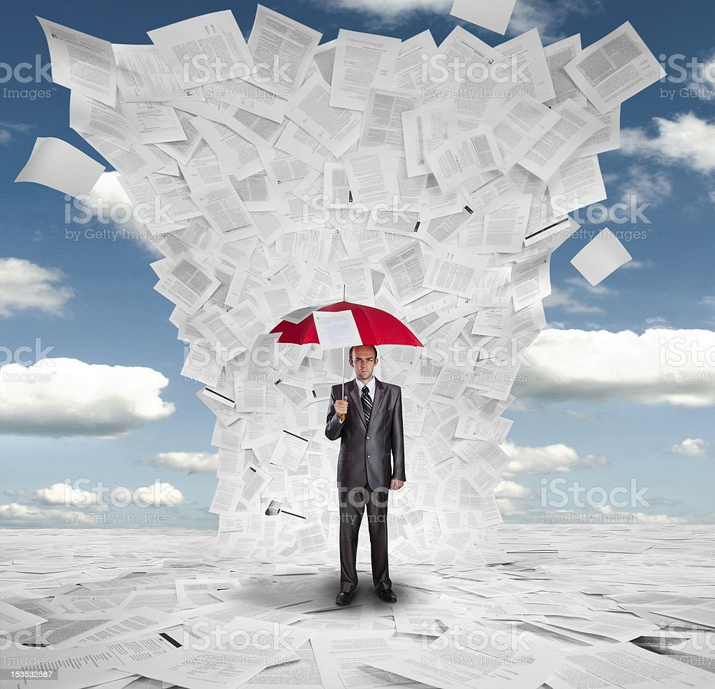 Businessman with red umbrella under huge wave of documents stock photo