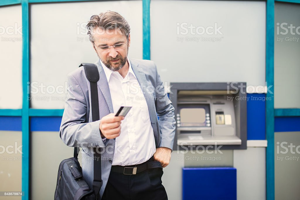 Businessman with rejected credit card next to cash machine. stock photo