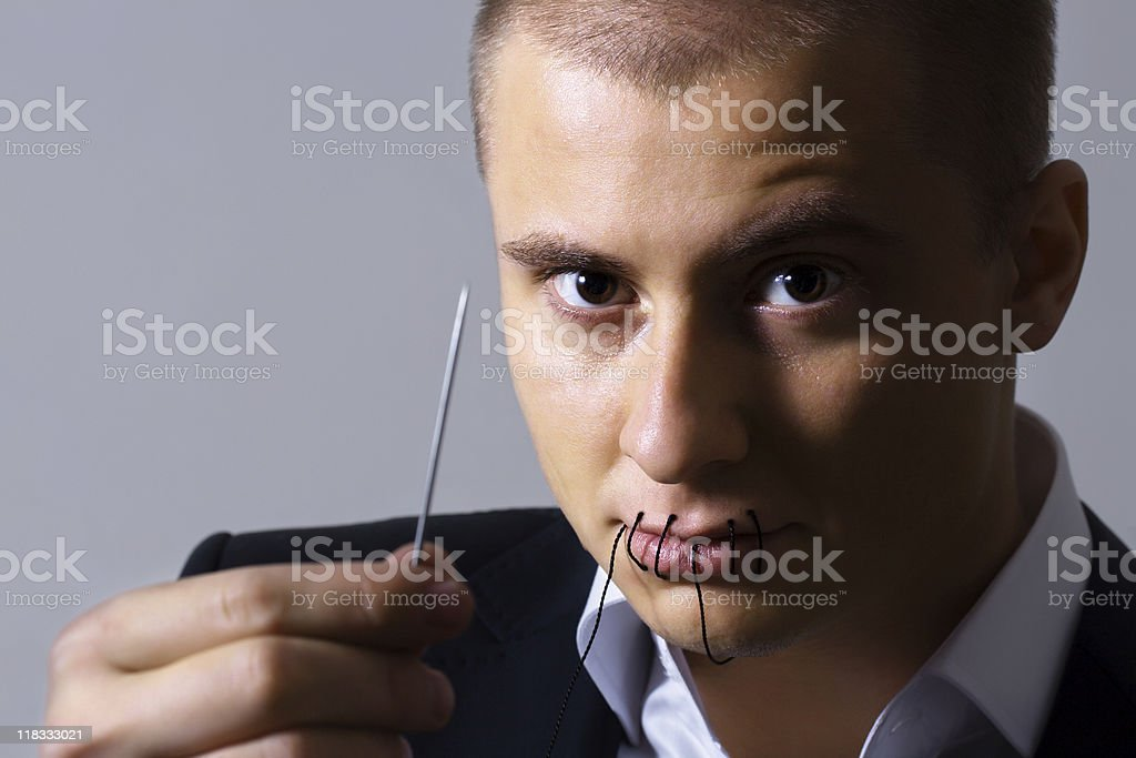Businessman with sewn mouth stock photo