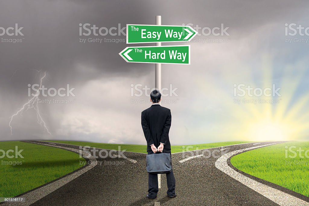Businessman with sign of easy vs hard way stock photo
