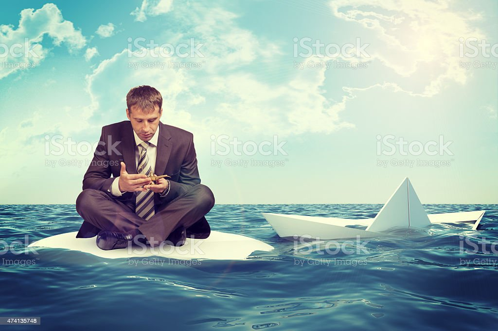 Businessman with sinking paper boat stock photo