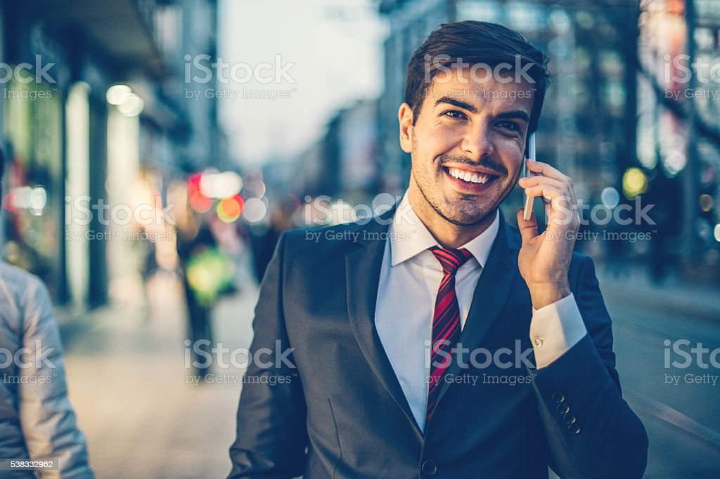 Businessman with smart phone and street lights stock photo