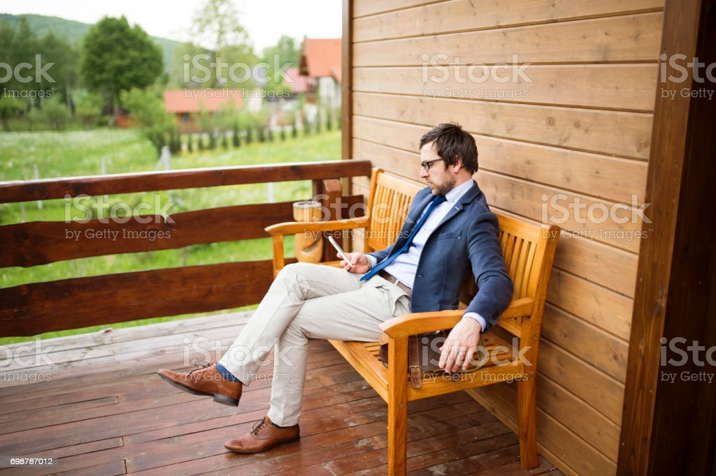 businessman with smart phone sitting on front porch stock ph