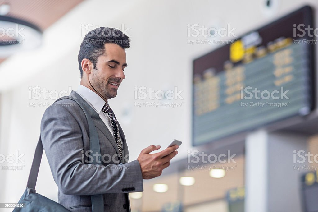 Businessman with smartphone at timetable at the airport stock photo