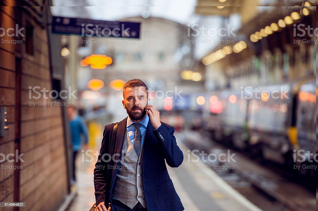 Businessman with smartphone, making a phone call, train platform stock photo