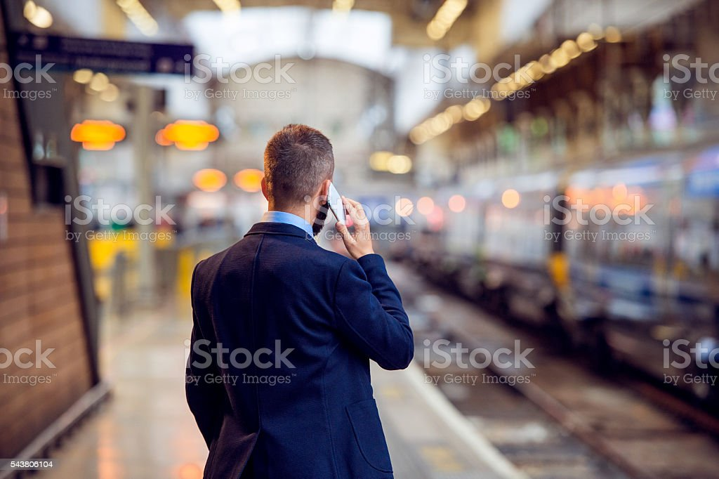 Businessman with smartphone, making a phone call, underground pl stock photo
