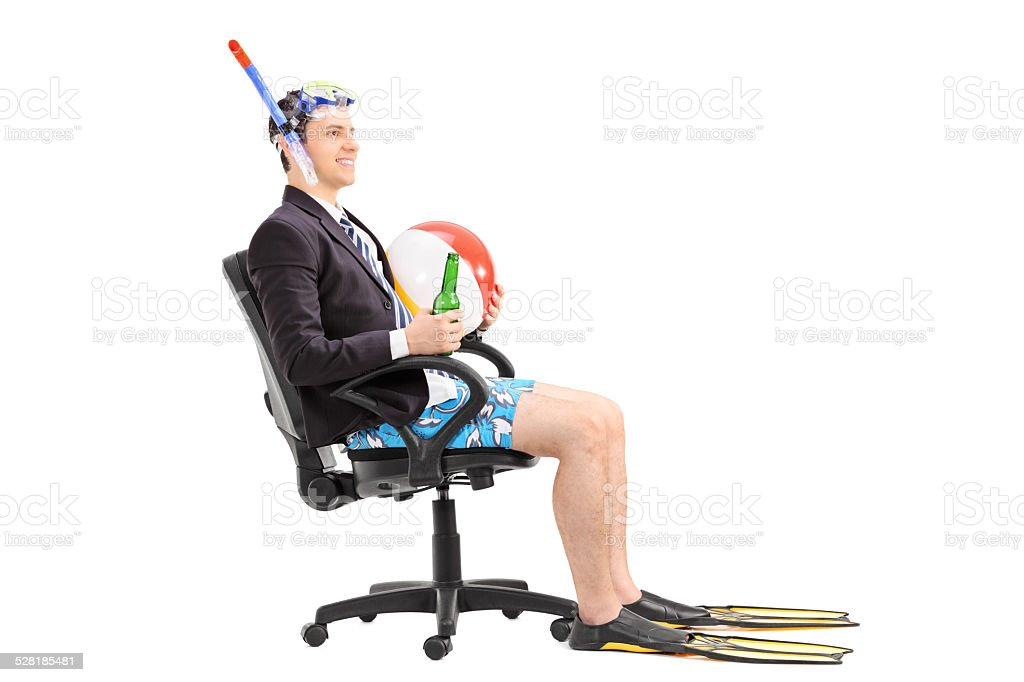 Businessman with snorkel sitting in an office chair stock photo