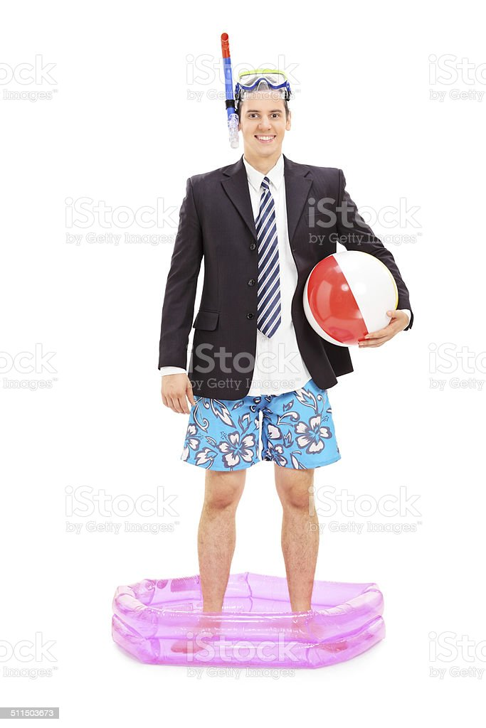 Businessman with snorkel standing in a small pool stock photo