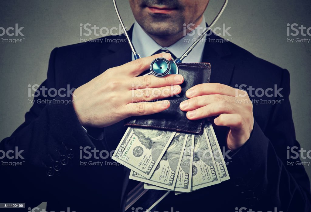 Businessman with stethoscope listening to wallet with dollar banknotes stock photo