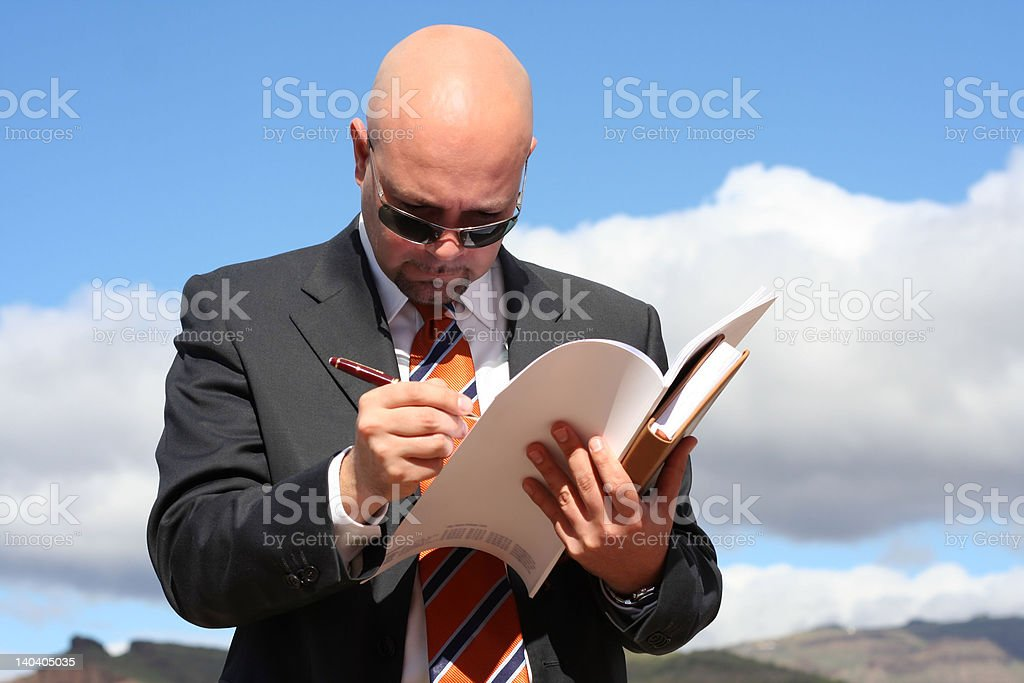 Businessman with suit and necktie writing in his newspaper royalty-free stock photo