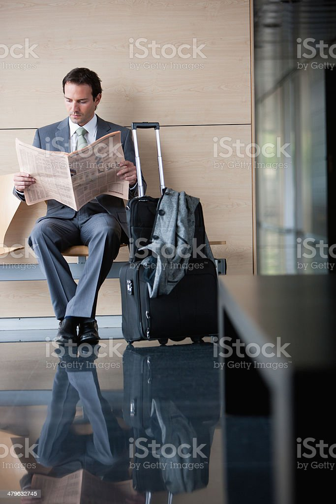Businessman with suitcase reading newspaper stock photo
