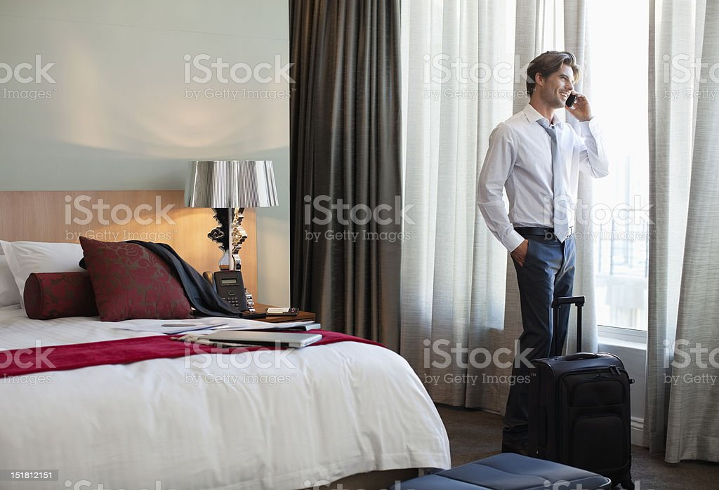 Businessman with suitcase talking on cell phone at hotel room window stock photo